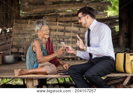 doctor advised the rural elderly to take the medicine correctly and to eat the whole panel Handsome pharmacist is offering a medication to a old female both are smiling