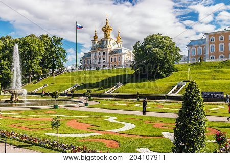 ST PETERSBURG, RUSSIA - July 07, 2017: Tourists in Peterhof the fountains of the Grand Cascade. The Peterhof Palace included in the UNESCO''s World Heritage List