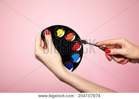 Artist's palette close-up. A palette of colors for painting makeup. Hand with manicure. Spatula artist