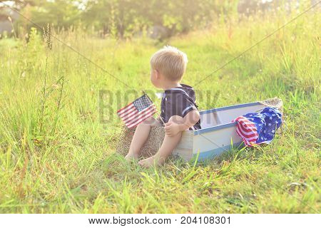 Boy in vintage blue sailor suit and american flag playing in wooden boat, pretending to sail across summer sea of grass. Adventure, children activity, game.