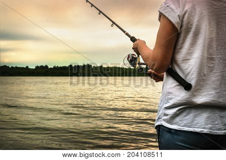 hands holding a fishing rod and twist the handle of the fishing reel at sunset. Shallow depth of field, soft focus
