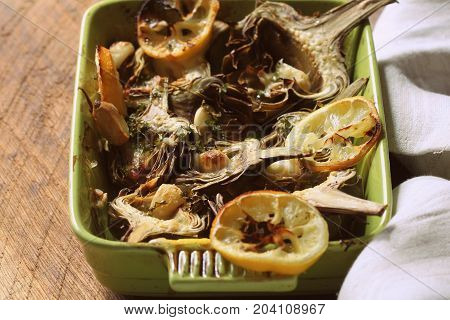 fried artichokes with garlic and lemon on pan on rustic table .