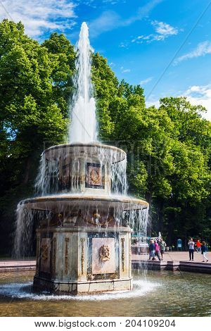 ST PETERSBURG, RUSSIA - July 08, 2017: Tourists in Peterhof the fountains of the Grand Cascade. The Peterhof Palace included in the UNESCO''s World Heritage List