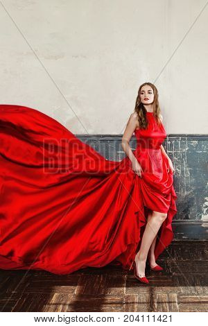 Elegant Woman in Red Blowing Dress. Beautiful Fashion Model on Blue Background