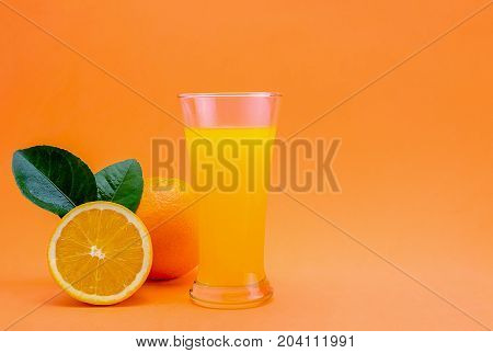 Orange juice in glass and fresh citrus around on orange background. Fruit product display or montage.