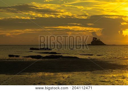 Beautiful sea sunset with small island silhouette on the beach at low tide & reflections in the sand.