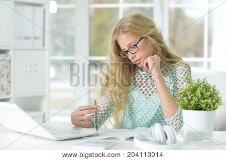 Portrait of cute teen girl sitting at table with laptop and doing her homework