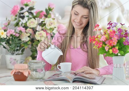 Beautiful young woman reading magazine  and drinking tea