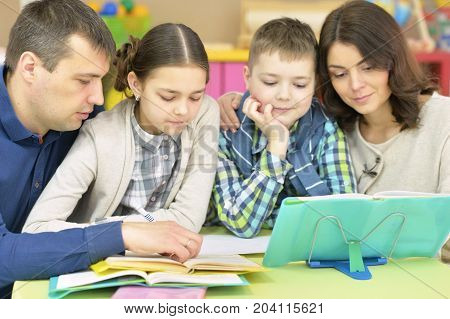 Parents helping their children with homework at home