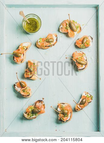 Crostini with smocked salmon, pesto sauce, watercress and capers over light blue background, top view, copy space, flat-lay. Party, catering or fingerfood concept