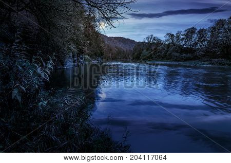 forest river in autumn mountains. lovely grassy shores with yellowed trees and rocky cliff. gorgeous nature autumnal scenery at night in full moon light