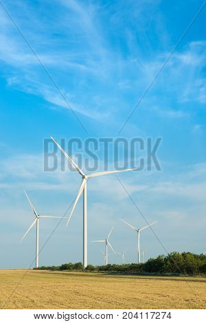 Wind mill in field with blue sky. Power and energy.