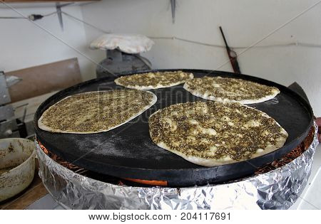 Four manaqeesh being baked on a saj oven the mankousheh is a famous Lebanese breakfast.