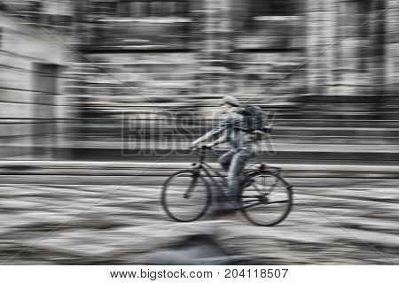 Speedy female cyclist with backpack and cap in town just after rain.