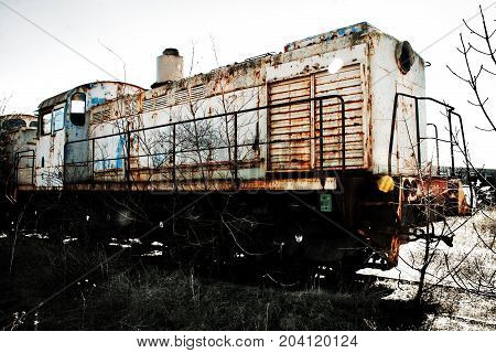 Old rusty train locomotive overgrown with trees.