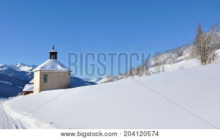 chapel of a french village in snowy hill