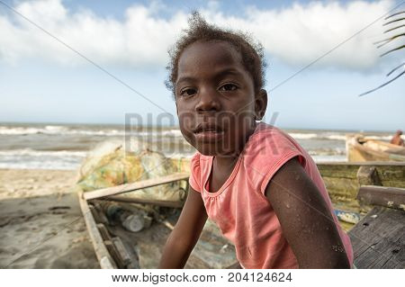 March 11 2015 Sambo Creek Honduras: a young garifuna girl part of the fishing community on the carribbean coast of the country sits on a dugout canoe