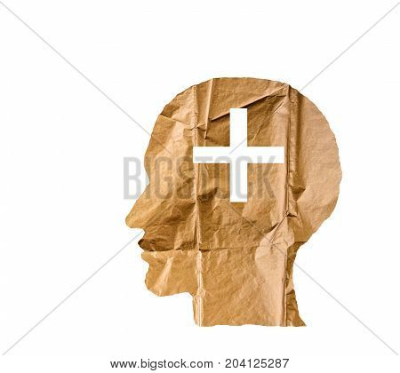 Crumpled paper shaped as a human head and plus sign on white background. Positive and plus sign concept.
