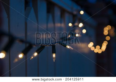 christmas lights in subdued light draped over residential fence