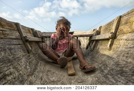 March 11 2015 Sambo Creek Honduras: a young garifuna girl part of the fishing community on the carribbean coast of the country inside a dugout canoe