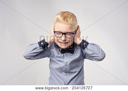 Isolated portrait of gaucasian boy covering ears with hands. Do not want to hear loud noise, conversation