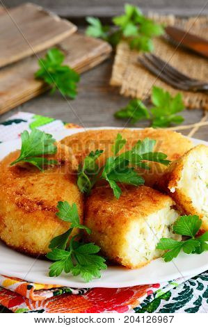 Stuffed vegetarian cutlets on a serving plate. Cutlets prepared from cauliflower and potatoes and stuffed with hard boiled sliced eggs. Closeup. Vertical photo