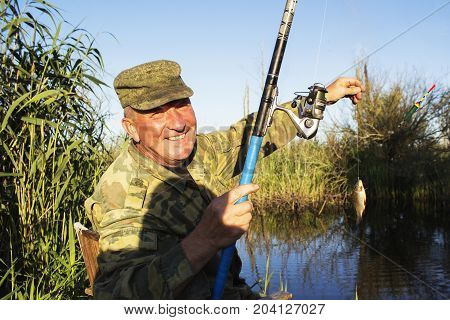 Happy mature fisherman with fresh caught crucian Carassius of family Cyprinidae on clear sky background