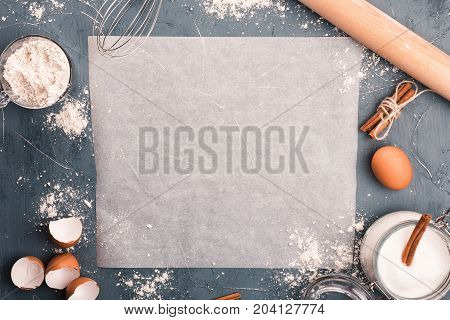 Sheet of baking paper on table. Food ingridients on kitchen board. Top view. Cope space