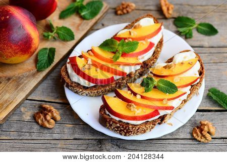 Rye bread sandwiches with soft cream cheese, nectarines, walnuts and mint on a serving plate and on a vintage wooden table. Recipe using rye bread. Closeup