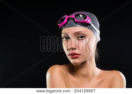Sports woman swimmer in a swimming cap, studio portrait, purposefulness