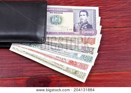 Bolivian money in the black wallet on a wooden background