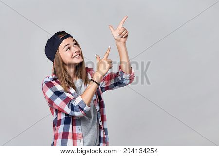 Teen girl pointing to the side up at empty copy space, over grey background