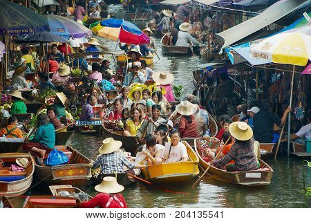 DAMNOEN SADUAK, THAILAND - MAY 15, 2008: Unidentified people enjoy boat tour at the floating market in Damnoen Saduak, Thailand.