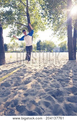 Concentrated Man Is Balancing On Slackline