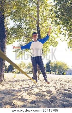 Man Is Looking Forward Concentratly, While Balancing On Slackline