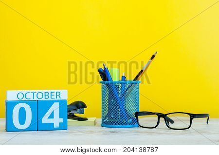 October 4th. Day 4 of month, wooden color calendar on teacher or student table, yellow background . Autumn time. Empty space for text.