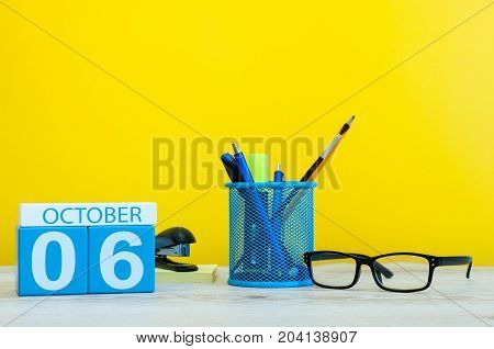 October 6th. Day 6 of month, wooden color calendar on teacher or student table, yellow background . Autumn time. Empty space for text.
