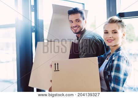 Couple With Cardboard Boxes In New House