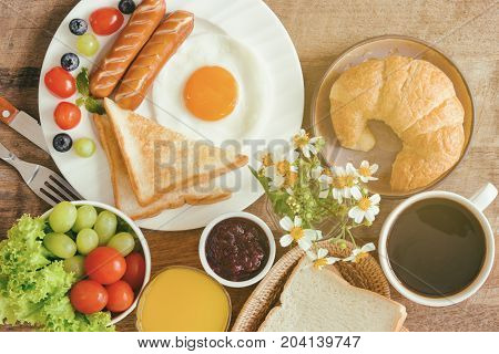 Homemade breakfast with sunny side up fried egg toast sausage fruits vegetable croissant strawberry jam coffee and orange juice in top view flat lay concept. Delicious american breakfast for family. American breakfast on breakfast table.