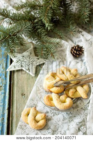 Pretzel with sugar in a New Year or Christmas decoration. Rustic style, selective focus.