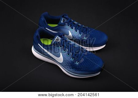 BURGAS, BULGARIA - SEPTEMBER 6, 2017: Nike Air Zoom Pegasus 34 Women's Running Shoes in blue on black background. Nike is a global sports clothes and running shoes retailer.