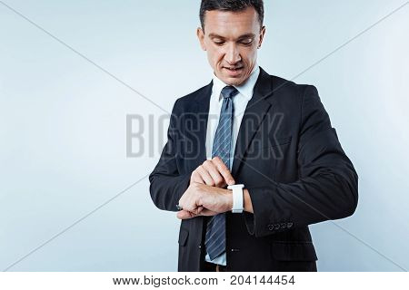 What time is it now. Waist up shot of a successful man looking at a dial of his wrist watch while standing over the background and rushing for work.