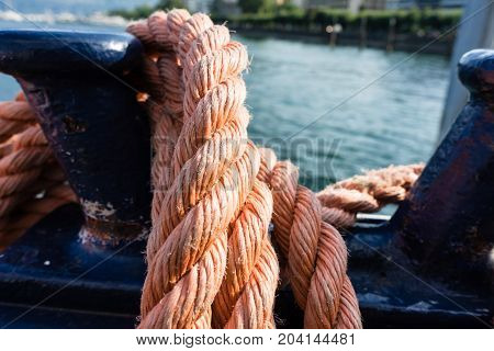 Close-up of an old red frayed boat rope, water background with landscape