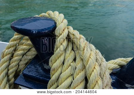 Close-up of an old yellow frayed boat rope, water background with landscape
