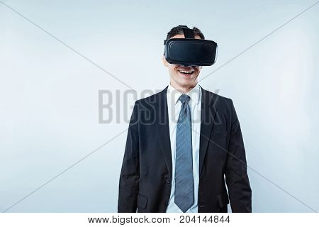 This looks so real. Waist up shot of an excited office worker wearing a black suit trying on a virtual reality headset over the light background.