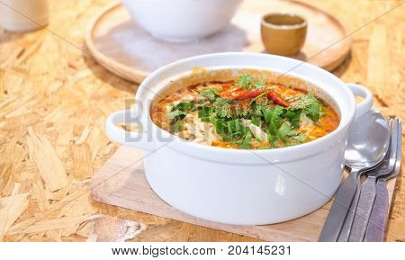 Delicious spicy noodles with coriander and vegetables on plywood dining table with copy space