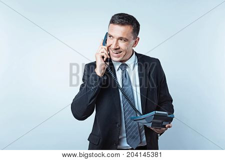 I like your idea. Waist up shot of a satisfied mature man wearing a black suit heaving a pleasant phone conversation and getting a good piece of news from a partner.