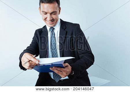 Thats interesting. Positive minded mature man in a black suit smiling while focusing his attention on a clipboard and looking through a written data.