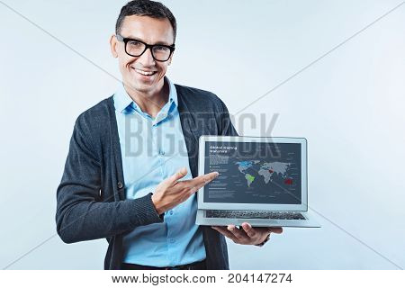 Waiting for you to join me. Friendly looking businessman in smart casual smiling into the camera while pointing toward a computer screen with a global map of trading transfers.