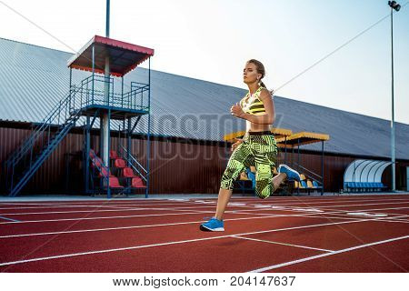Young, beautiful girl athlete in sportswear runs along the treadmill. Sport background. Outdoor stadium
